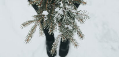 Girl standing in the snow holding fir tree branches
