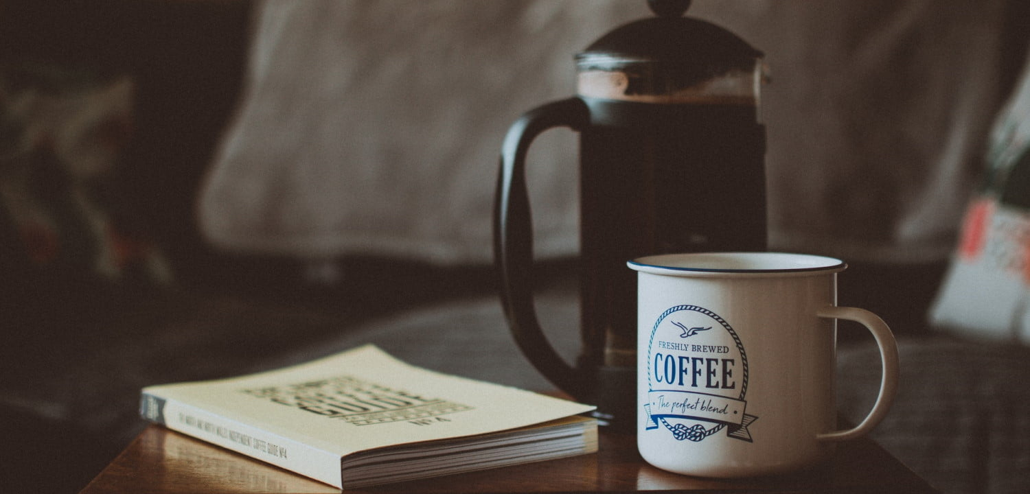 French press, coffee cup, and a book