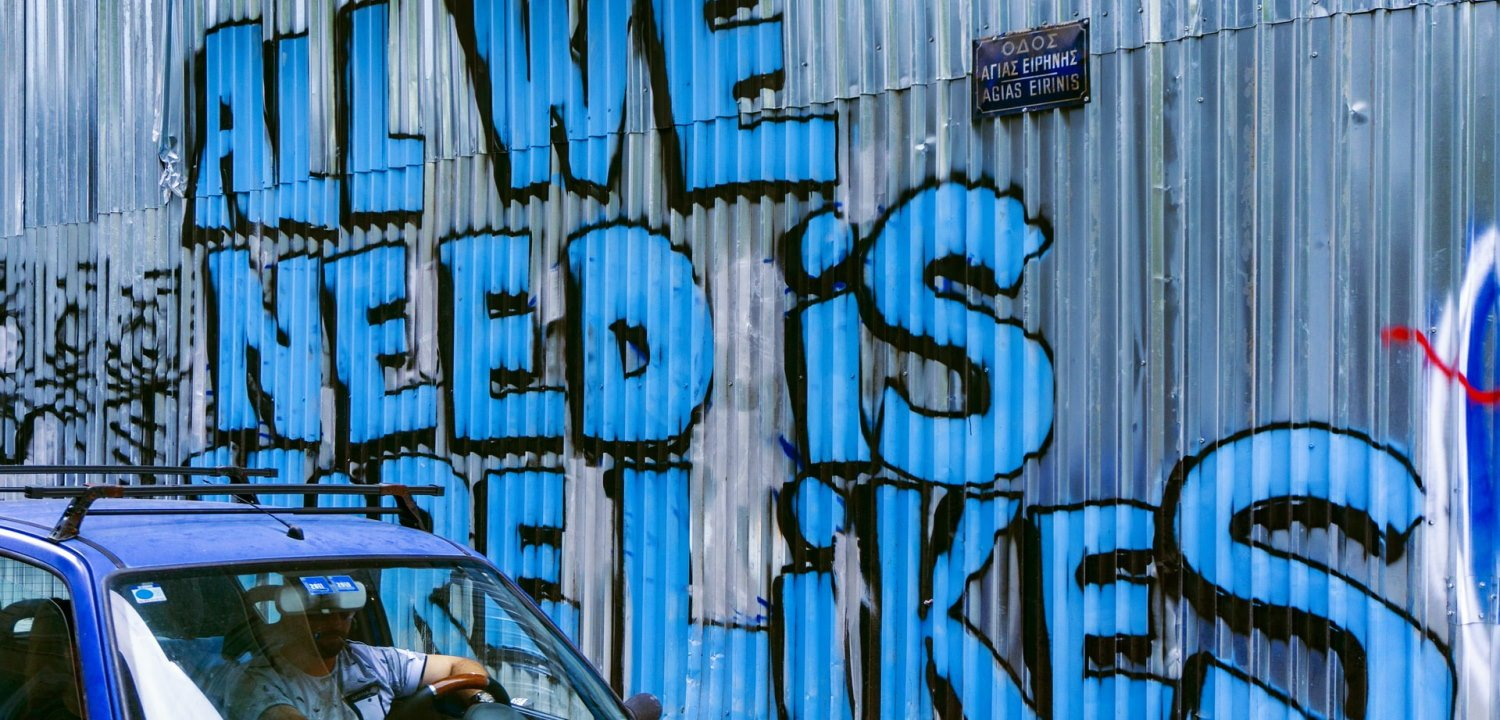 Graffiti in Facebook blue colour, saying 'All we need is more likes'